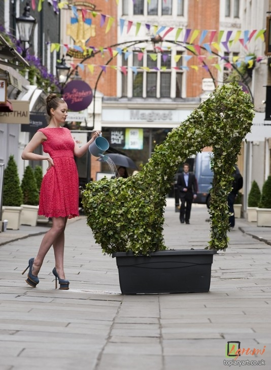 Monique Cockerill poses with the giant topiary stiletto shoe in St Christopher's Place, London. Picture by GLENN COPUS