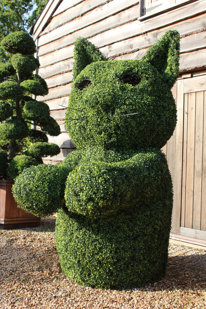 Artificial boxwood cat in front of workshop