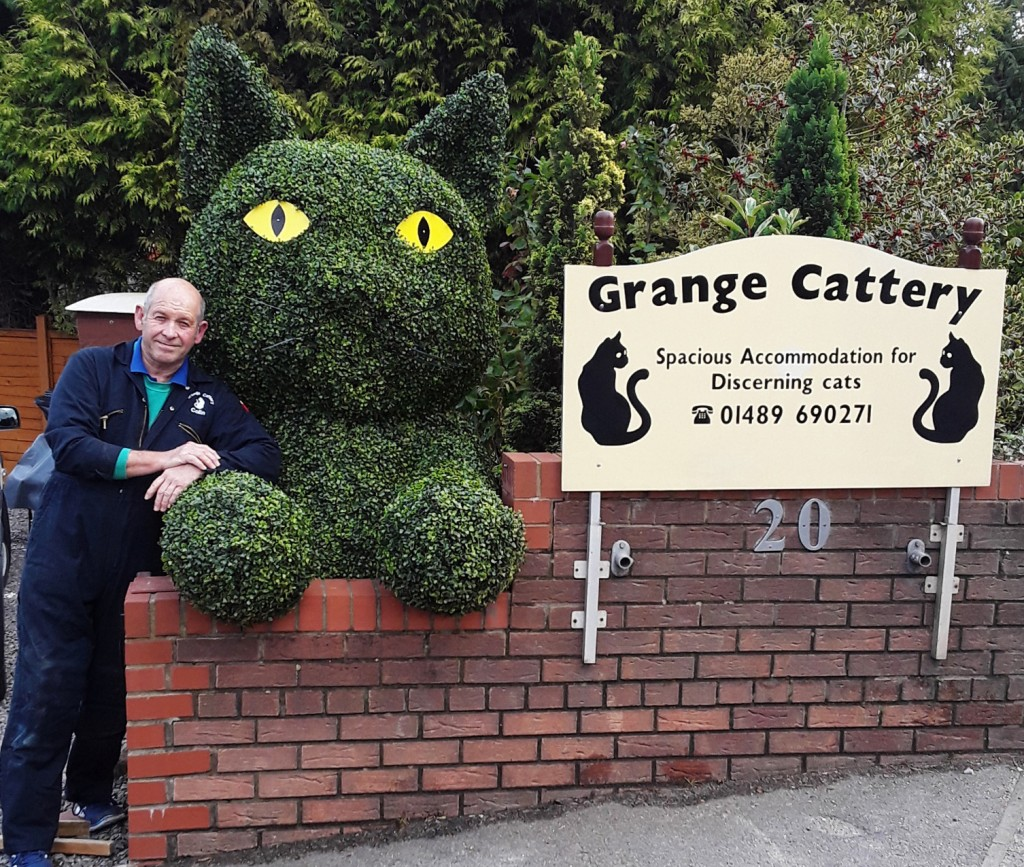 Complete topiary cat in front drive
